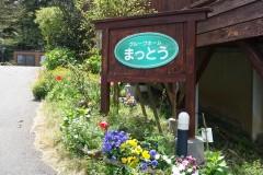 ロッジ風の建物を季節の草花や案内版がお出迎え。